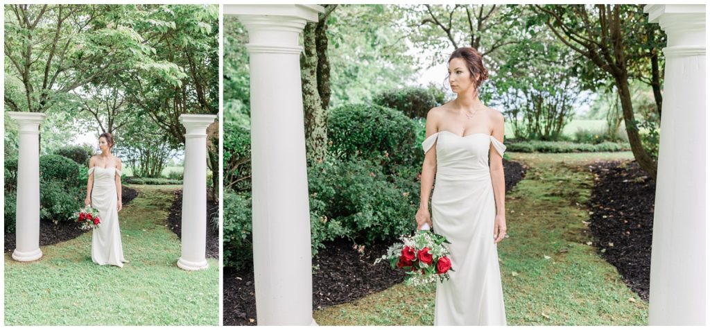 bride in a white off the shoulder gown with a slit up the thigh holds her red rose wedding day bouquet while walking through a fairytale garden